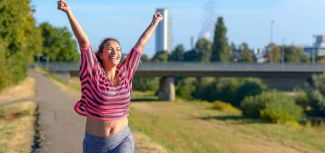 Happy fit woman cheering and running