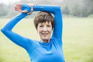 Middle aged women stretching her arms