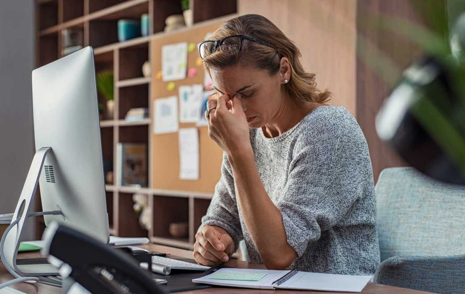 Woman having headache at computer