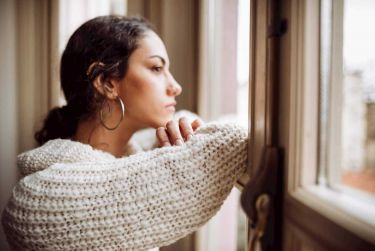 Pensive woman in front of window